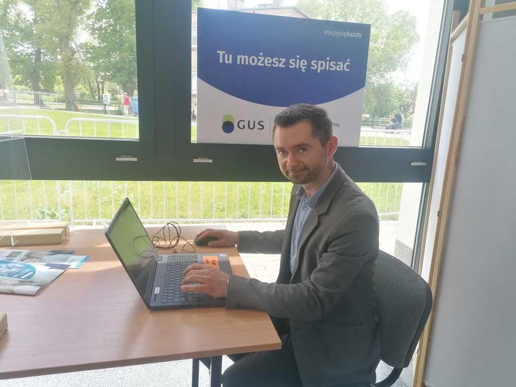 na zdjęciu znajduje się Wójt Gminy Murów siedzący przed laptopem w miejscu wyznaczonym w Urzędzie Gminy do samospisu