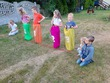 grupa dzieci w kolorowych workach przygotowujących się do zawodów pn. skoki w workach