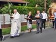 Korona dożynkowa, gospodarze dożynek z księdzem i mieszkańcami w drodze do kościoła (1)